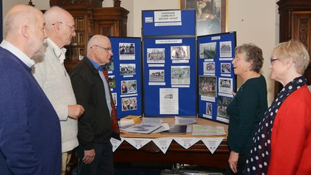 Members of Fakenham's three history groups discuss one of their exhibits. From left: Harry Yates (G