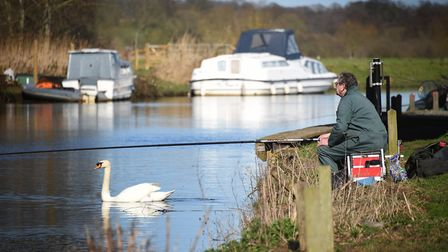 A fisherman and swan enjoying the warm spring weather at Beccles.Picture: ANTONY KELLY