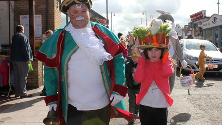 Town crier Andrew Cunningham-Brown leading the parade with bonnet competition winner Florrie Robbins