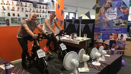 Midwich staff Tom Hawes and Donna Coleman taking part in a fundraising exercise bike challenge for N