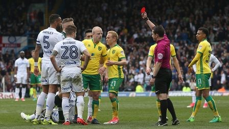 Referee Tony Harrington issues a red card to Steven Naismith of Norwich and sends him off by for his
