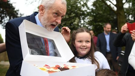 Ella Thurtle, nine, presents Labour leader Jeremy Corbyn with a box of cakes at the James Paget. Pho