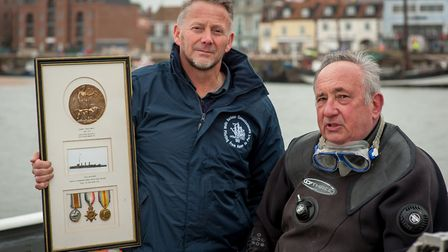Dive leader Dave Lock with Robert Smith, pictured with the historic death penny, commemorative scrol