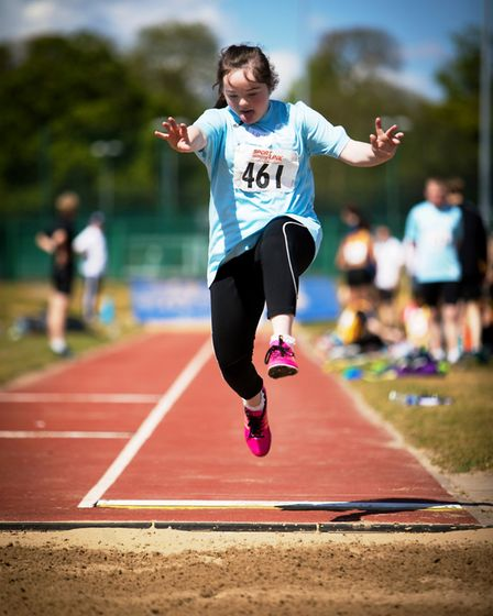 Lily Edwards taking junior girls' gold in the long jump. Picture: Michael Lyons
