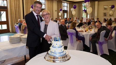 Andy and Sylvia Aitken cutting their wedding cake, paying tribute to the bus that helped bring them