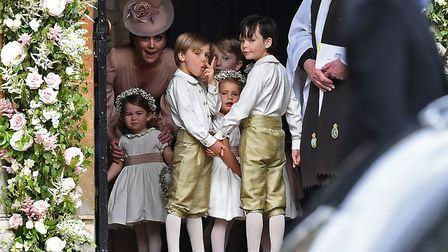 The Duchess of Cambridge, left, stands with her daughter Princess Charlotte, bottom left, as they ar