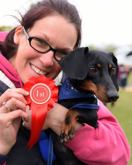 Faye Denney with her dachshund, louis, and the first place rosette for winning the dog that looks mo