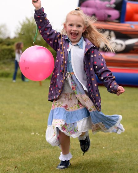 Yazmin Feek, seven, plays with her balloon at the Rose May Fete at Ringsfield near Beccles. PICTURE:
