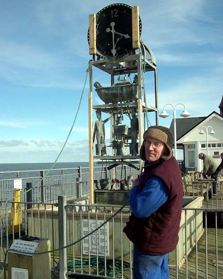 Tim Hunkin putting his popular water clock back in place on Southwold Pier. Photo: David Lennard.