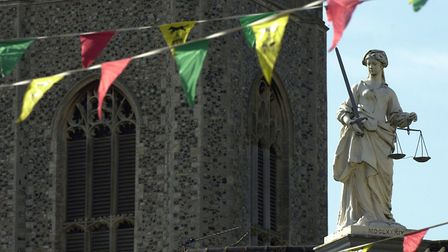 The statue of Justice on top of Bungay Buttercross against the tower of St Mary's Church. Picture: