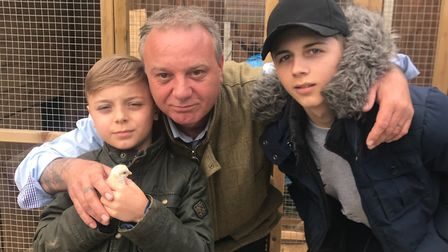Mark Overton with his sons and four-legged Speedy, who was hatched on their Norfolk smallholding. P