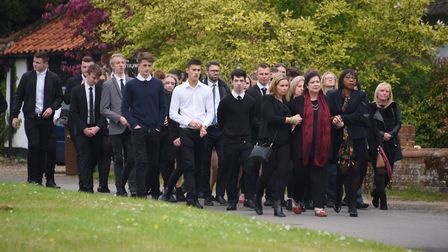 Young people walk behind Dominic O'Neill's coffin with his family, including mother Davina, at his f