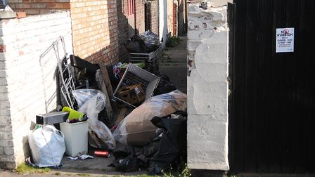 Rubbish dumped in a North Lynn alleyway - next to a sign warning offenders will be prosecuted. Pictu