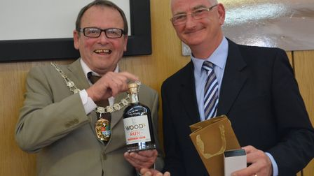 New chairman Richard Shepherd presenting former chairman John Lee with a bottle of rum as he bows ou