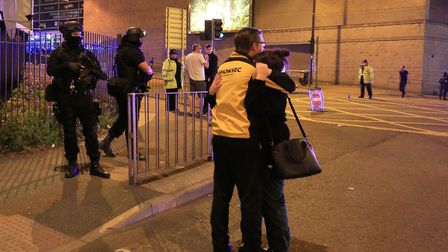 Armed police (left) at Manchester Arena after reports of an explosion at the venue during an Ariana