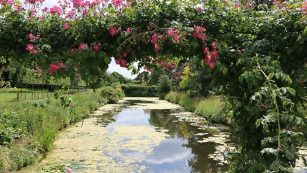 The lovely moat at Hindringham Hall could be seen through rose arches and wild flowers along the edg