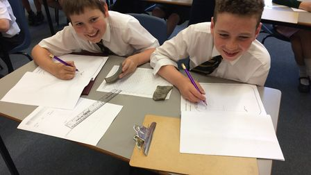 Arlo, 10, and Henry, 11, from Thetford Grammar School working on pottery recording as the school hos
