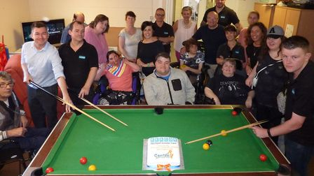 SEACON staff join Centre 81 members and staff in the games room to mark the new link between the com