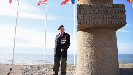 Normandy veteran Alan King from Suffolk on Juno beach by the memorial, where he landed on D-Day. Pic