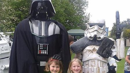 Darth Vader and a Storm Trooper from the East Anglian Star Wars Society with children at the Little