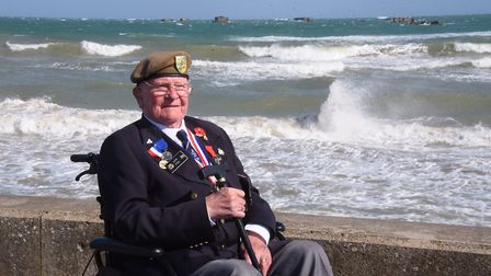 Normandy veteran Len Fox at Asnelles by part of the remains of the Mulberry Harbour amid the rough s