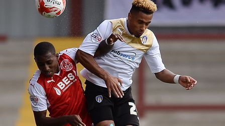 Amari'i Bell of Fleetwood Town, left, challenging Colchester defender Richard Brindley in a League O
