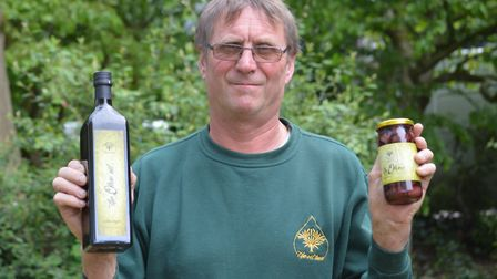 Jerry Cox of The Oil Tree, with olive oil produced on his farm in Greece. Pic By Chris Hill