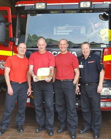 Earlham Fire Station's 'green watch' crew with Linda Cullum's cake. Picture: Norfolk Fire and Rescue