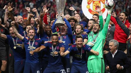 Manchester United's Wayne Rooney lifts the trophy as his team-mates celebrate winning the UEFA Europ