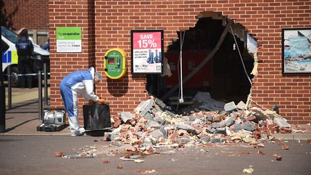 A scene of crime officer working outside the Co-op store on Polka Road in Wells, that was hit by ram