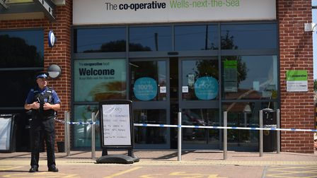 A PCSO stands outside the Co-op store on Polka Road in Wells, that was hit by ram raiders in the ear