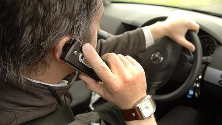 A unidentified driver using a mobile phone whilst driving in Norwich. Picture: James Bass For: