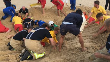 Emercency services battle to retrieve the dummies buried below the sand as part of the hole collapse