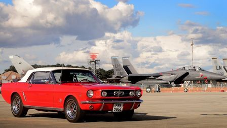 A 1965 Ford Mustang convertible sits near a F-15 Strike Eagle at RAF Lakenheath for their Wings and