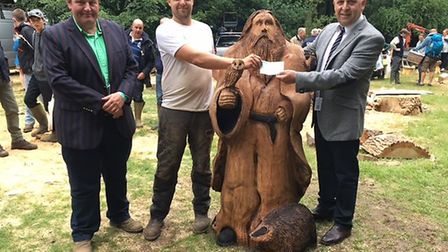Judge Daniel Price with wood carver Arnie Barton and Graham Andrews of TMA Bark. Picture: Andrew Sto