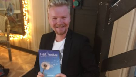 James McDermott with the Holt Festival brochure. Pictured at Wells Deli in Holt, where he works par