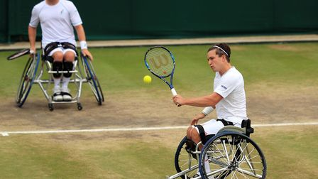 Gordon Reid plays a backhand volley with partner Alfie Hewett in the background. Picture: PA