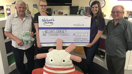 A cheque for £1,000 is presented to Sarah Hyde at Nelson's Journey's Smile House. Pictured: Brian S