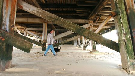 A man and his dog walking below the timbers of Claremont Pier in Lowestoft. Picture: BILL DARNELL
