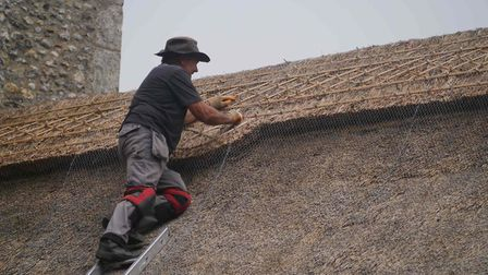 A thacter on the roof of St. Peter's Church, Brunstead. Picture: Michael Pollitt