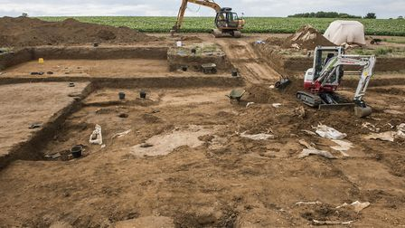 A trench being dug to reveal the clay ovens beneath the soil, used for cereal processing in the Angl