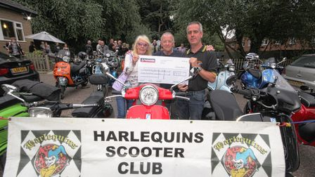 Janet Money, from Dereham Cancer Care, receives a cheque from Harlequins Scooter Club Mid Norfolk. P