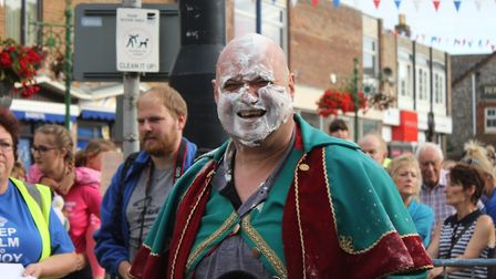 Sheringham town crier Andrew Cunningham-Brown gets a pasting in the carnival street races. Picture:
