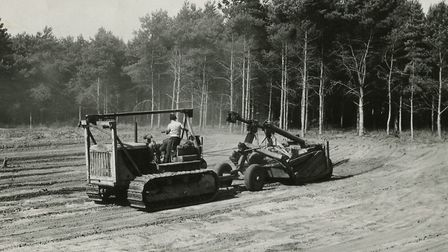 A catterpillar tractor connected to a mechanical scraper makes speedy work of excuvating the site of