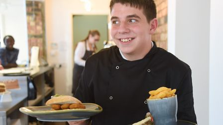 Apprentice chef, Bray Wade, serves a meal at the Mitre pub and café which has reopened in Earlham Ro