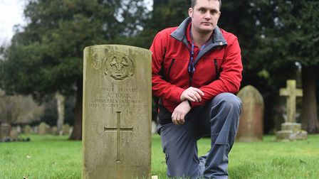 Liam Young at the grave of Pte Alfred Back in Dereham cemetery. Picture: Ian Burt