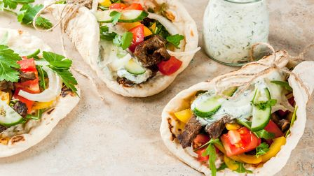 Traditional Greek wrapped sandwich gyros - tortillas, bread pita with a filling of vegetables, meat