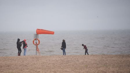 A family on the empty beach as the wind and rain hits Great Yarmouth sea front. Picture: DENISE BRAD