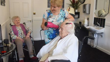 Carol Quinton, mobile hairdresser, does 90-year-old Alex Cooley's hair in the salon at the Beeches C