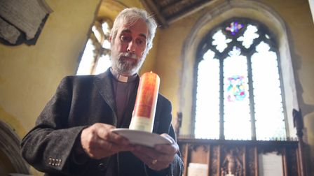 Canon Steve Wright lighting a candle at Banham Church for murder victim Peter Wrighton. Picture : AN